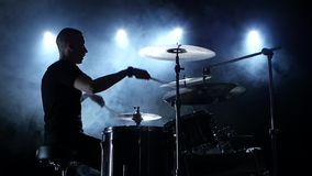 Musician plays a melody on the drums. Black smoke background. Side view. Silhouettes. Slow motion stock footage