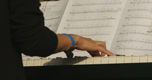 Musician plays the piano, white keys in the foreground. Musical score blurred background stock video