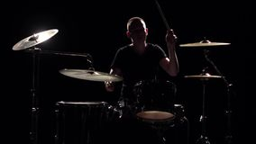 Musician plays professionally good music on drums using sticks. Black background. Silhouette. Slow motion stock video footage