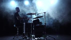 Musician plays professionally good music on drums using sticks. Smoky background. Silhouette. Slow motion stock video
