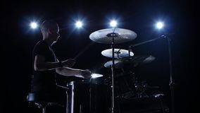 Musician plays professionally music on drums. Black background. Side view. Back light. Silhouette stock footage
