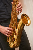 The musician plays a saxophone. The musician in black plays a saxophone Royalty Free Stock Photography