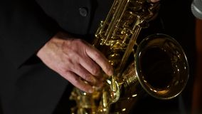 The musician plays the saxophone. Close up of the fingers pressing the keys of the instrument. Male musician playing the saxophone. Close up of the fingers stock footage