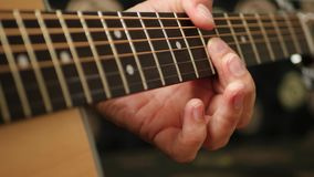 The musician plays solo on a yellow acoustic guitar. The fingers of a musician on the fretboard of a guitar close-up, the concept of music and creativity. 4k stock footage