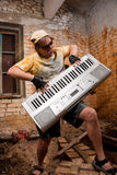 Musician plays a synthesizer. In abandoned industrial interior Royalty Free Stock Image