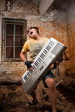 Musician plays a synthesizer. In abandoned industrial interior Royalty Free Stock Images