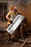 Musician plays a synthesizer. In abandoned industrial interior Stock Photography