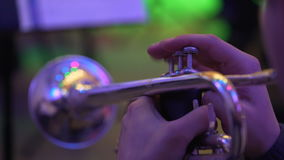 The musician plays the trumpet in the concert hall. Musical instrument close-up. The musician plays the trumpet in the concert hall. musician playing musical stock footage