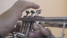 The musician plays the trumpet in the concert hall. Musician playing musical instrument. close-up stock footage
