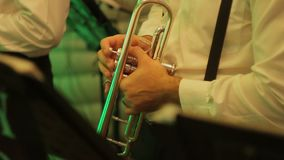 Close up of hand playing trumpet. Brass instrument in a band. Musician plays trumpet in concert at night close up stock video footage