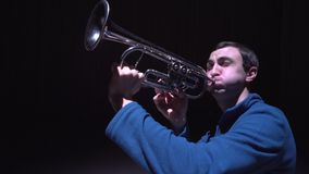 A musician plays the trumpet, isolated black background stock video