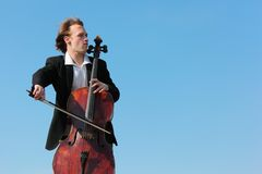Musician plays violoncello against  sky Royalty Free Stock Photo
