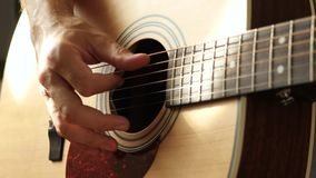 The musician plays a yellow acoustic guitar, close-up at the guitar deck. The concept of music and creativity. 4k stock video footage
