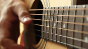 The musician plays the yellow acoustic guitar, touching the string with his finger. Guitarist finger close up. 4k stock video