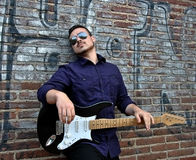 Musician posing with his guitar Stock Photography