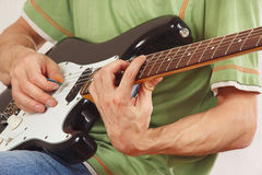 Musician put fingers for chords on electric guitar close up Royalty Free Stock Images