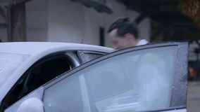 Musician puts his accordion in a car stock video footage