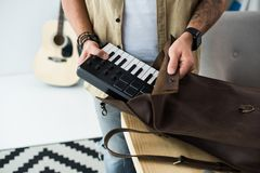 Musician putting MPC pad into bag. Cropped shot of musician putting MPC pad into bag royalty free stock image