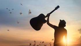 Musician raising guitar over head free birds of silhouette. Musician holding guitar in hand with free bird of silhouette on sunset nature background royalty free stock photo