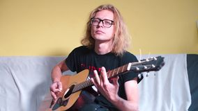 Musician rehearses on an acoustic guitar before performing at a concert. Musician with long hair rehearses on an acoustic guitar before performing at a concert stock video footage