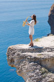 Musician on rocky seashore Stock Image