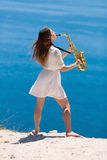 Musician on rocky seashore. Girl playing on saxophone on open air Stock Photos