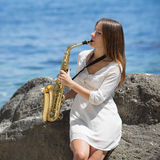 Musician on rocky seashore Stock Photos