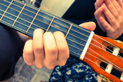 Musician's fingers on guitar fretboard while playing classic guitar Stock Photo