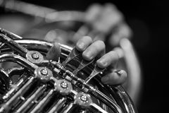 Musician's fingers playing the french horn Stock Photos