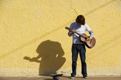 Musician on Sidewalk. Young male musician alone on the sidewalk with guitar Royalty Free Stock Photography