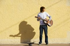 Musician on Sidewalk. Young male musician alone on the sidewalk with guitar Stock Photography