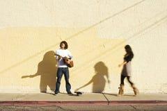 Musician on Sidewalk and Woman Pedestrian Stock Photos