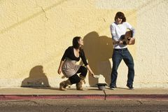 Musician on Sidewalk and Woman Pedestrian Stock Photography