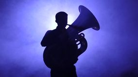 Musician in silhouette playing in tuba, smoky studio. Slow motion stock video footage