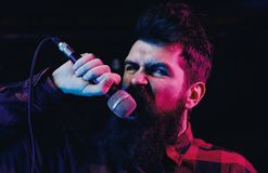Musician, singer singing in music hall. Man with agressive face holds microphone, singing song,. Black background. Singer concept. Musician with beard and Royalty Free Stock Photography