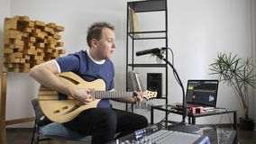Musician singing and playing electric guitar in home music studio. Professional musician recording electric guitar in digital studio at home. He is singing and