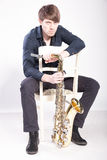 Musician sitting on chair and holding saxophone Royalty Free Stock Photos
