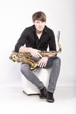 Musician sitting with saxophone Stock Photography