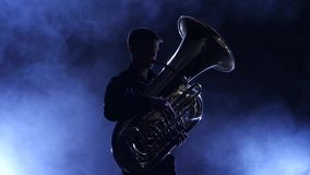 Musician in a smoky studio playing in a tuba, silhouette stock video footage