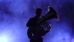 Musician in smoky studio playing in tuba, silhouette. Slow motion stock video footage