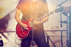 Musician on stage playing on guitar Royalty Free Stock Image