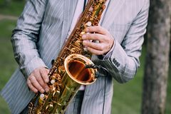Musician suit performs melody saxophone outside summer. Musician in a suit performs a melody on a saxophone from the outside in the summer Royalty Free Stock Images