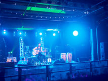 Musician Tavana play guitar and sing on stage in blue light. HONOLULU, HI - FEBRUARY 22: Musician Tavana play guitar and sing on stage in blue light at stock photo