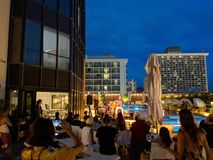 Musician Tavana on stage by pool at Hyatt Centric Waikiki as crowd watches. Honolulu - June 8, 2018: Musician Tavana sings and plays guitar on stage by pool at royalty free stock images