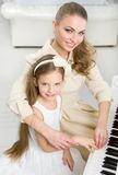 Musician teaches little girl to play piano Stock Photos