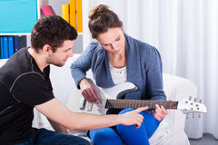 Musician teaching his girlfriend playing guitar Stock Photography