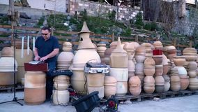 For playing on clay pots, the musician tunes his instruments. The musician tunes the sound with a tuning fork and other devices stock video footage