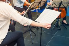 Musician turn the page of Music notebook on stand with background of playing cellists and violinists band on event. Commercial mus. Ic. Service at business Stock Image