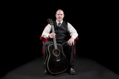 Musician in vest and tie sitting in red velvet chair holding guitar stock image