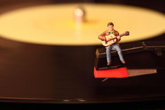 Musician vinyl record G. Miniature model of guitarist sitting on a vinyl record Stock Images